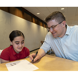 Wish School mentor helps student with homework